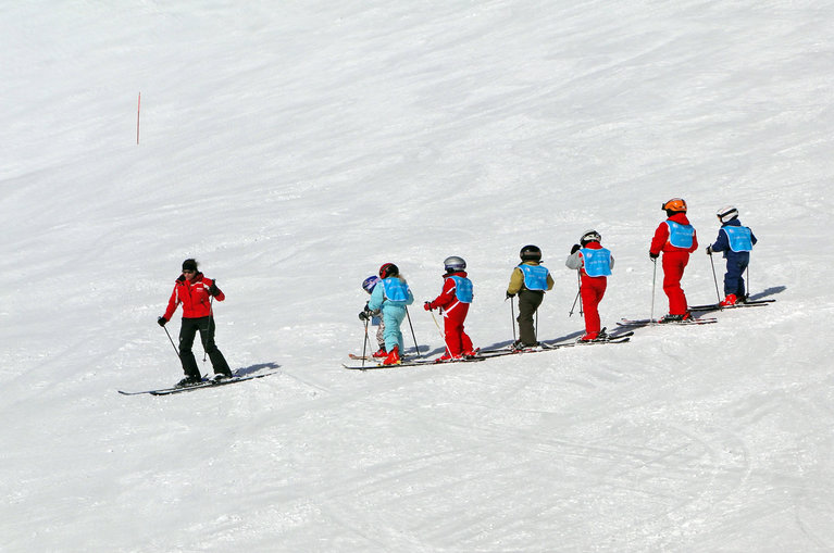 children following an instructor on a ski slope