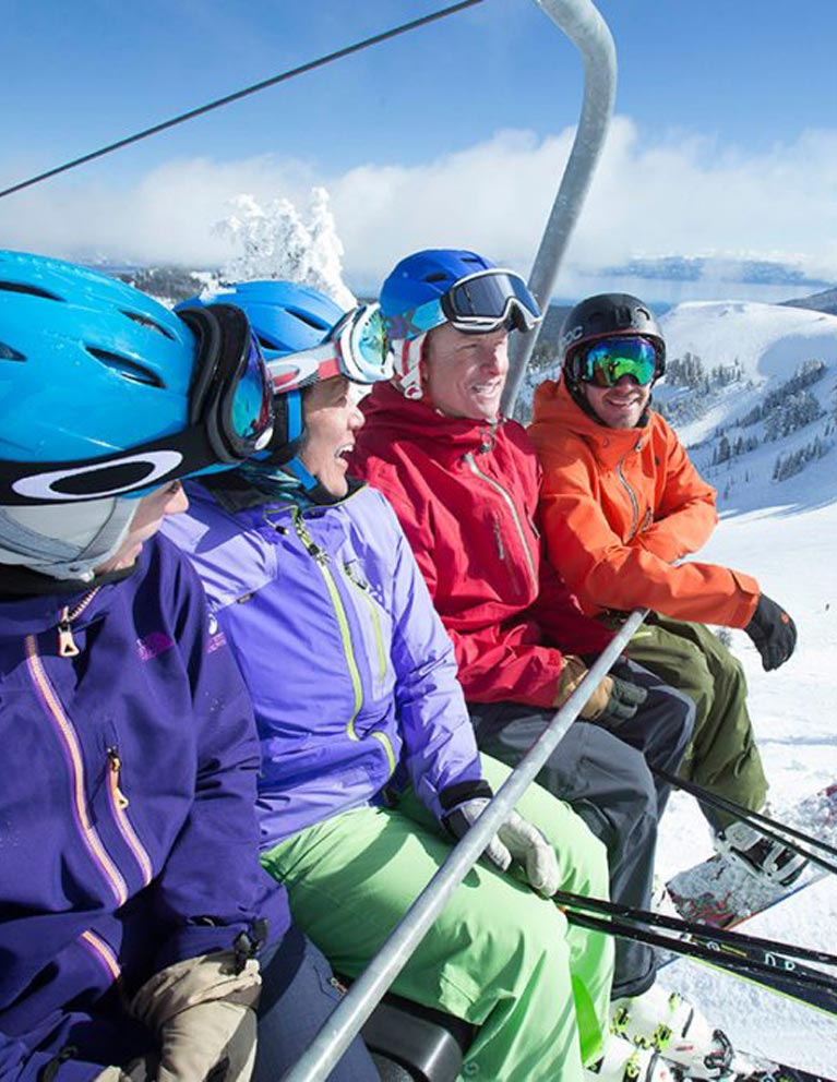 Three people on a chair lift for a ski mountain