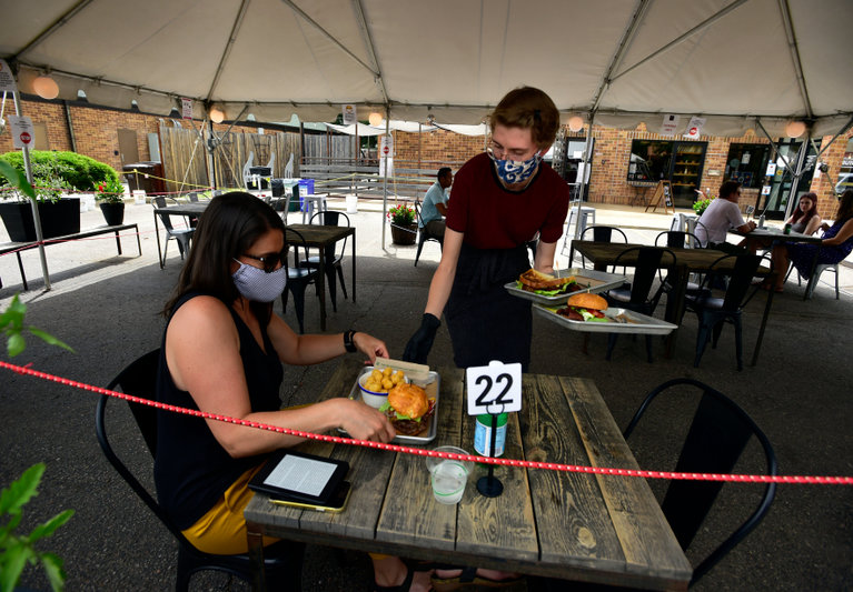 People dining outdoors wearing masks